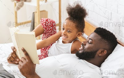 Cute african girl listening to fairy tale, dad reading book to his child