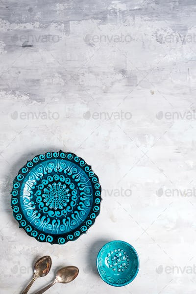 Turkish ceramics decorated blue plate and bowl with spoons on stone background, top view