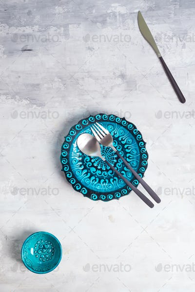 Turkish ceramics decorated blue plate and bowl with new luxury black cutlery on stone background