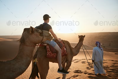 Camel riding in desert at sunset