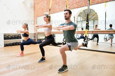 People training legs using trx at gym