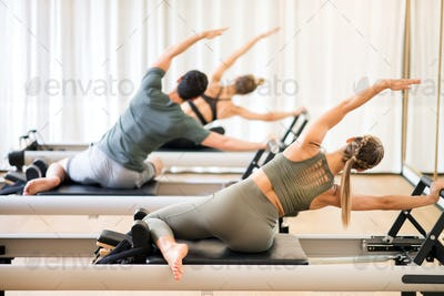 Group of people doing the mermaid pilates exercise
