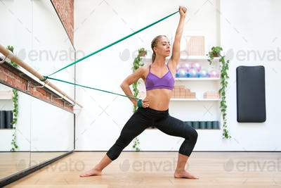 Young fit woman exercising with flex band at gym