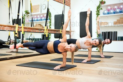 People training elbow side planks with trx at gym
