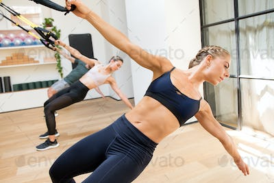 Class doing Trx power pull exercises in a gym