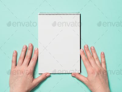 Blank paper notebook and female hands