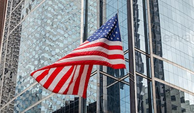 American flag in Chicago, Illinois downtown. Glass facade buildings background.