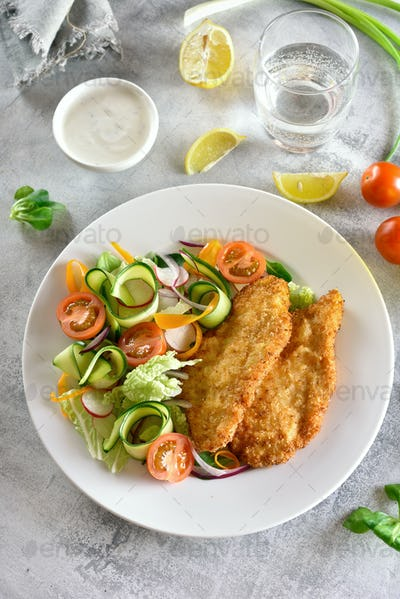 Vegetable salad and breaded chicken breast