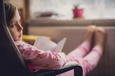 Girl in pyjama reading a book