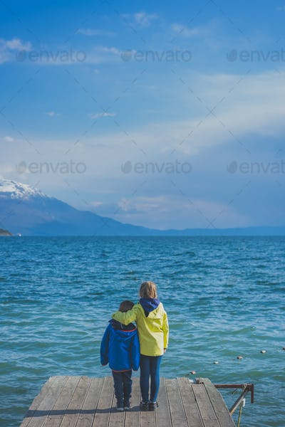 Little girl embracing her brother by the lake