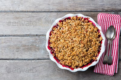 Berry Crumble in White Baking Dish on Grey Wooden Background. Top View. Copy Space