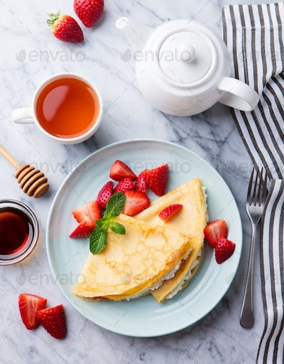 Crepes, Thin Pancakes with Fresh Strawberry and Ricotta, Cream Cheese. Marble Background. Top View