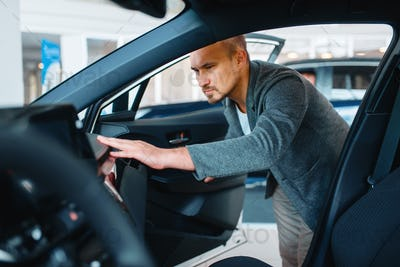 Man watching the interior of new car in showroom