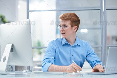 Young multi-tasking office manager looking at computer screen