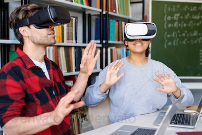 Young astonished man and woman in vr headsets having virtual experience