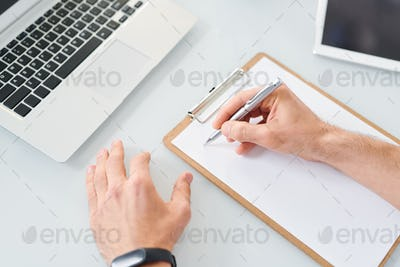Young designer or economist with pen going to make notes or sketch