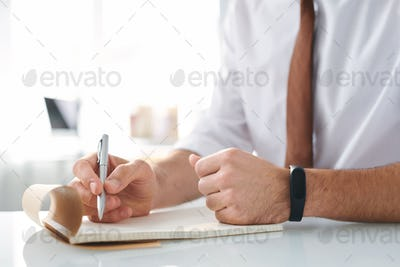 Hand of designer with pen over blank page of notepad