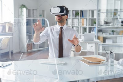 Elegant businessman in vr headset pointing at transparent computer screen