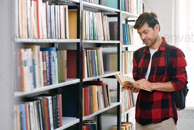 Young handsome student reading one of books in college library by shelf