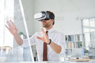 Young businessman with vr goggle watching virtual presentation