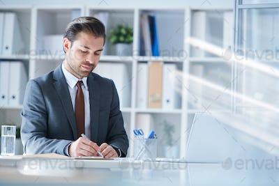Serious analyst in formalwear writing down working points