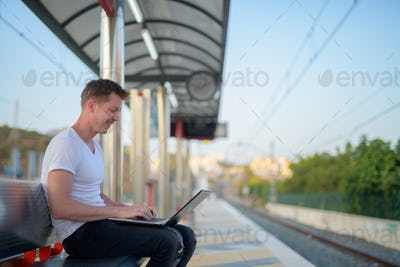 Happy man using laptop computer at train station platform while sitting
