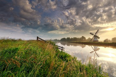 sunrise over Dutch windmill by river