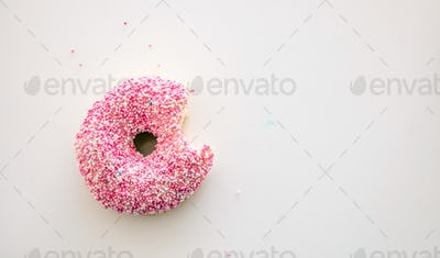 Doughnut with pink and white decoration isolated on white color background. Top view