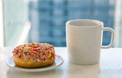 Doughnut and coffee cup on white color table. Closeup view