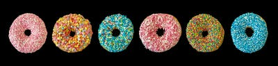 Doughnuts with colorful decoration isolated on black color background. Top view