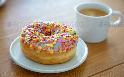 Doughnut and coffee cup on wood. Close up view
