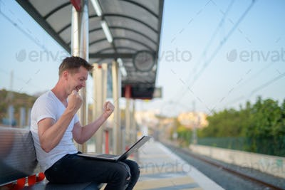 Happy man using laptop computer at train station with arms raised
