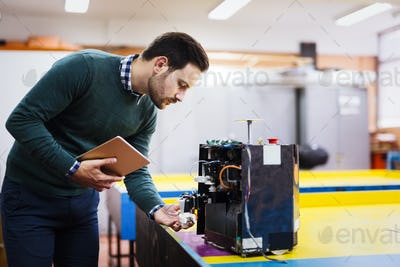 Young student of robotics working on project