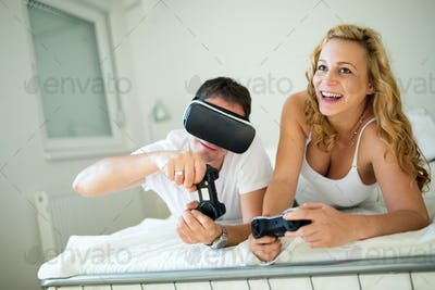 Attractive couple enjoying playing games with vr goggles
