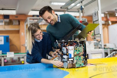 Young attractive students of mechatronics working on project