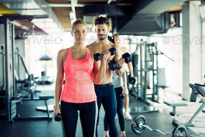 Personal trainer helping young woman with exercises for biceps