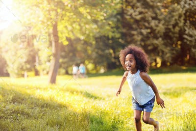 Portrait of happy little girl running on grass land