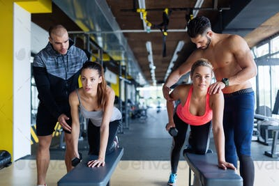 Young women in gym doing exercises with trainers