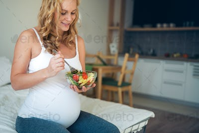 Portrait of pregnant woman eating healthy food