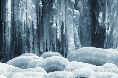 icicles on frozen waterfall in winter background