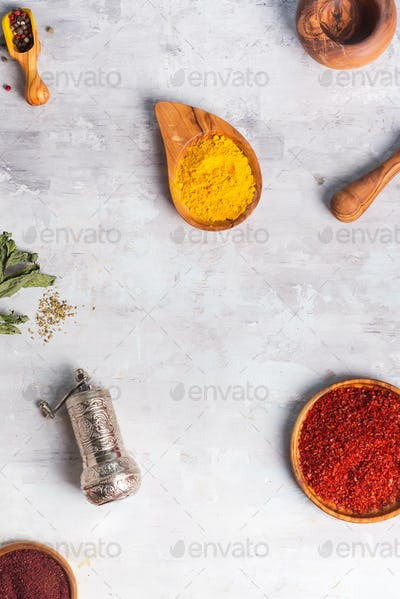 kinds of spices of different grinding in wooden bowl with handle grinder on stone , flat lay