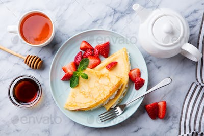 Crepes, Thin Pancakes with Cream Cheese, Ricotta and Fresh Strawberries. Marble Background.