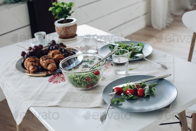Table with healthy tasty breakfast surrounded by modern interior at summer morning