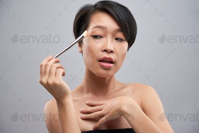 Woman applying make-up on her eyes
