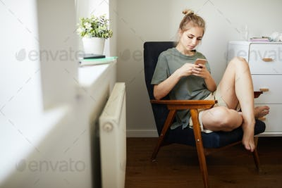 Cute girl in casualwear watching video in smartphone