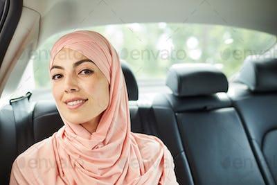Beautiful Muslim woman on backseat