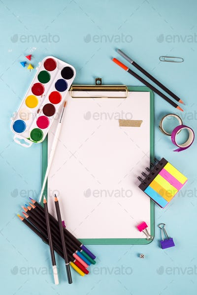 Clipboard and office or school supplies over blue background, flat lay. Back to school