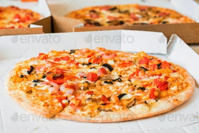 Delicious pizza with tomatoes, mushrooms and shrimps in paper box and two more pizzas in background