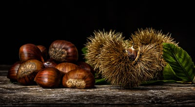 Chestnuts and chestnut bur on wooden table.