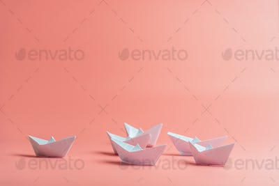 Origami paper boats over pink